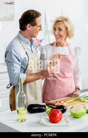 smiling senior couple clinking with glasses of wine during cooking at kitchen and looking at each other - Stock Photo