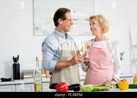 happy senior couple clinking with glasses of wine during cooking at kitchen and looking at each other - Stock Photo