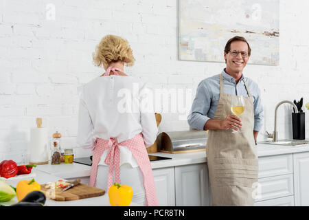 elderly man in apron holding glass of wine and smiling at camera while cooking with wife in kitchen - Stock Photo