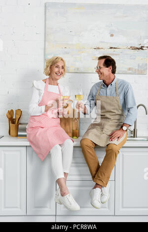 happy senior couple in aprons holding glasses of wine while sitting together in kitchen - Stock Photo