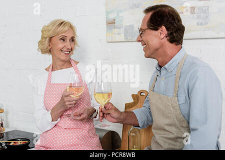 happy old couple in aprons holding glasses of wine and smiling each other in kitchen - Stock Photo