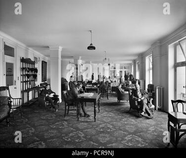 YMCA reading room, Exeter Hall, Strand, London, 1907. An interior view of the reading room in the YMCA's headquarters. The site of Exeter Hall is now occupied by the Strand Palace Hotel. The YMCA was founded in 1844 to provide Christian fellowship for clerks and shop assistants, but quickly expanded to serve a much wider public. - Stock Photo