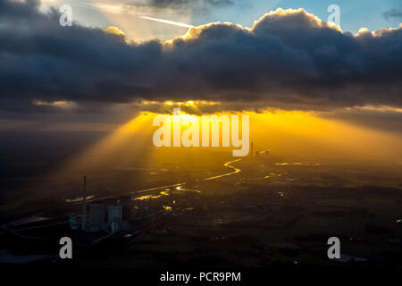 STEAG coal power plant Bergkamen on the Datteln-Hamm-Canal in the evening light, smog, haze, hazy weather, inversion weather, back light, golden light, industrial romance, sun shining through cloud hole on the power plant, Bergkamen, Ruhr area, North Rhine-Westphalia, Germany - Stock Photo