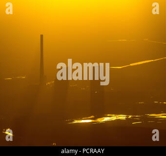 STEAG coal power plant Bergkamen at the Datteln-Hamm-Canal in the evening light, smog, haze, hazy weather, inversion weather, back light, golden light, industrial romance, sun shining on the power plant through cloud hole, Bergkamen, Ruhr area, North Rhine-Westphalia, Germany - Stock Photo