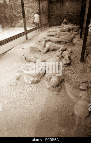 Plaster casts of victims in the moment of their death at the Garden of the Fugitives in Pompeii, near Naples, Italy - Stock Photo