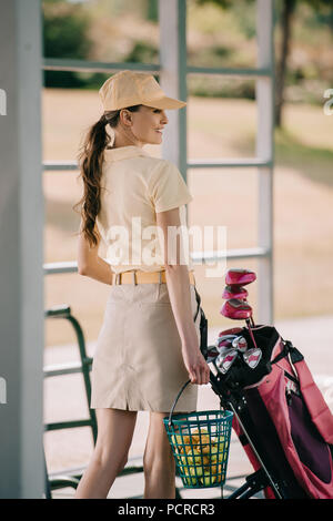 side view of smiling woman in polo and cap carrying golf equipment at golf course - Stock Photo