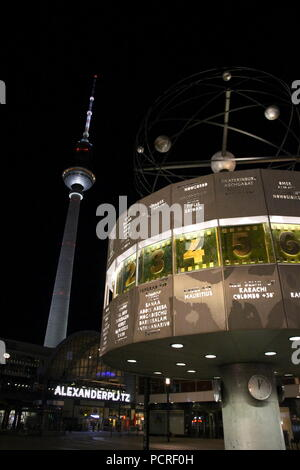 World Clock at Alexanderplatz in Berlin by night. - Stock Photo