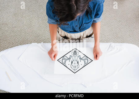 overhead view of female fashion designer choosing print for empty white t-shirt at ironing board - Stock Photo