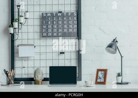 Laptop with blank screen on table in modern office - Stock Photo