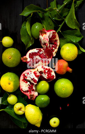 lemon on a branch and limes. chopped grenade. on a black background. dark photo. water drops. wet fruit - Stock Photo