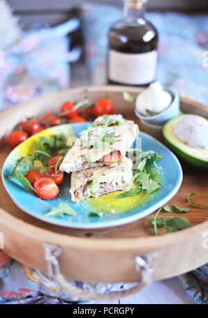 roll of pita bread on the grill. stuffing with fish and salad. avocado and olive oil. dinner on a wooden tray. healthy food - Stock Photo
