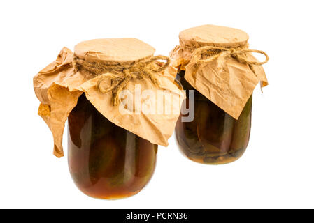 Glass jars with canned homemade cucumber with tomato sauce - Stock Photo