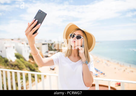 Pleasant girl in sunglasses touching her cheek while making selfie on sea background - Stock Photo