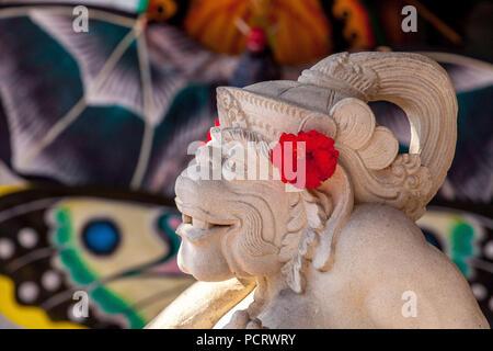 Monkey god Hanuman carved from stone with red hibiscus flowers, white limestone, Hanuman, Hinduism, Hindu, Ubud, Bali, Indonesia, Asia - Stock Photo