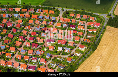 Aerial view, new housing estate, brick buildings with red tiled roofs, single-family houses and terraced housing, home gardens, Billerbeck, Münsterland, North Rhine-Westphalia, Germany - Stock Photo