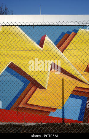 The coloured wall of a switch house or a high-voltage system behind a fence - Stock Photo