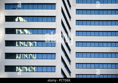 Abstract reflections of surrounding buildings in the windows of a modern skyscraper - Stock Photo