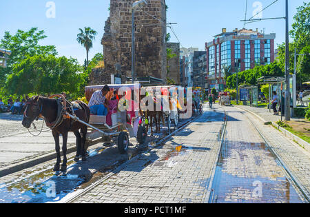ANTALYA, TURKEY - MAY 11, 2017: The row of horse-drawn carriages parked along the tramlines and antique ramparts of Republic street, on May 11 in Anta - Stock Photo