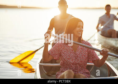 Smiling young woman enjoying a day canoeing with her boyfriend and another couple on a lake on a late summer afternoon - Stock Photo