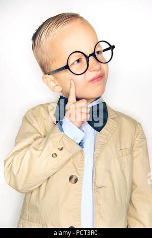 Cute little blonde boy wearing a suit, bowtie and glasses deep in thought while standing against a white background - Stock Photo