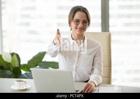 Smiling businesswoman greeting job candidate asking to sit - Stock Photo