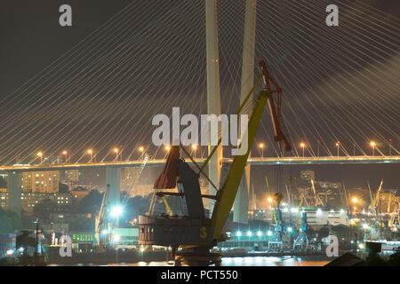 Vladivostok, Russia-August 4, 2018: Large crane on the background of the Golden bridge at night. - Stock Photo
