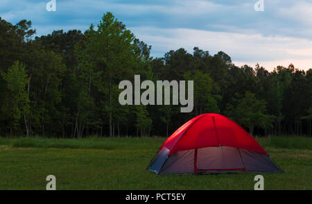 Small backpacking tent set up at a treeline as the sun is setting on a cloudy day - Stock Photo