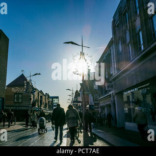 Shoppers walking along a high street, doing Christmas shopping. Christams decorations adorn street lights. - Stock Photo