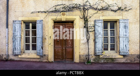 House facade in Coursan, wooden door, plant, window and shutters - Stock Photo