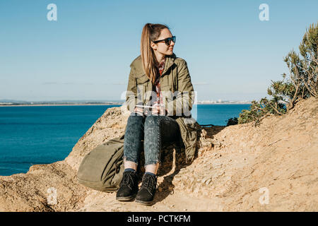 A young beautiful girl or tourist uses a tablet to look at a map or mobile application or something else. - Stock Photo