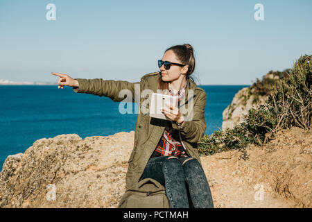 Young beautiful girl or tourist uses a tablet and shows a hand in the distance. Ocean or sea in the background. - Stock Photo