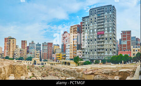 Panorama of stone foundation of ruined Greek Serapeum Temple with the high-rises of Karmouz on background, Alexandria, Egypt. - Stock Photo