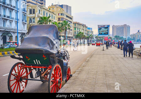 ALEXANDRIA, EGYPT - DECEMBER 18, 2017: Romantic ride on horse-drawn carriage along the sunset Corniche Avenue with a view on sea, palm trees, old mans - Stock Photo