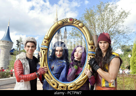 LAKE BUENA VISTA, FL - NOVEMBER 10:  The cast of Disney Channel Original Movie 'Descendants' (L-R: Cameron Boyce who plays Carlos, Dove Cameron who plays Mal, Sofia Carson who plays Evie, and Booboo Stewart who plays Jay) perform Nov. 10, 2015 during the taping of the 'Disney Parks Unforgettable Christmas Celebration' TV special in Magic Kingdom park at Walt Disney World Resort in Lake Buena Vista, Florida.  People:  Descendants - Stock Photo