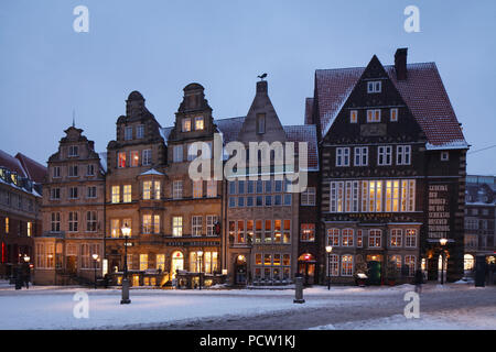 Historic row of houses with snow at the market square with market square West side at dusk, Bremen, Germany, Europe - Stock Photo