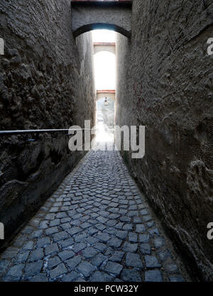 Germany, Bavaria, Upper Bavaria, Neuötting, narrow lane, paved, gloomy - Stock Photo