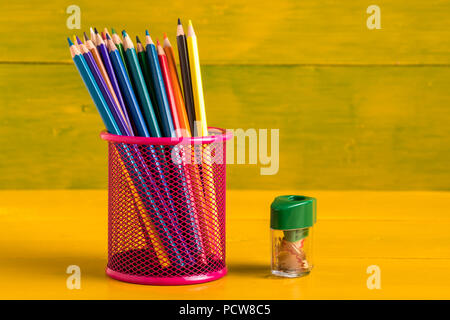 color pencils in metal grid container on the yellow board. - Stock Photo