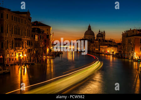 Long exposure of a vaporetto travelling down the Venice's Grand Canal at dusk as seen from the Accademia Bridge - Stock Photo