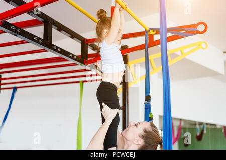 Little girl hanging on the crossbar, mom supports - Stock Photo