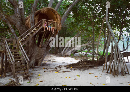 Happy children have fun on family holidays walk. Kids, mother sit on balcony edge of tree house dangling legs, look at sea beach through jungle. - Stock Photo