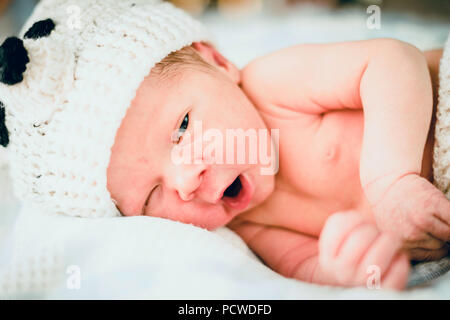 The newborn baby boy dressed in bear-like light clothes - Stock Photo