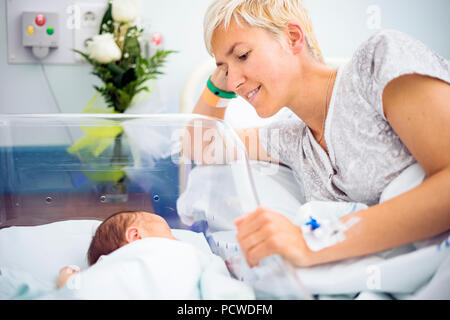 Mother looking with love at her newborn baby boy still in the hospital - Stock Photo