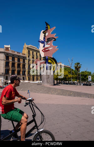 Cyclist passing in front of the El Cap de Barcelona, a surrealist sculpture created by American Pop artist Roy Lichtenstein for the 1992 Summer Olympi - Stock Photo