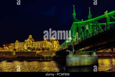 The Liberty Bridge in Budapest with the Art Nouveau style historical building of Gellert spa on the bank of Danube River in Budapest,Hungary,at nignt - Stock Photo