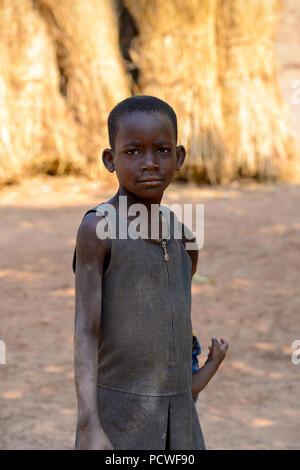 GHANI, GHANA - JAN 14, 2017: Unidentified Ghanaian little serious girl in a local village. Ghana people suffer of poverty due to the bad economy. - Stock Photo