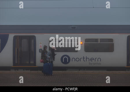 Passengers leaving an Arriva  Northern rail train at  Wigan North Western railway station with the Northern rail logo visible - Stock Photo