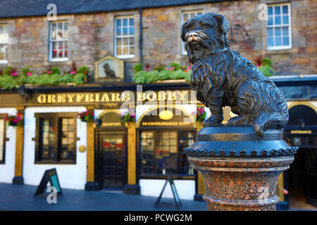 Statue of Greyfriars Bobby the famous Skye Terrier dog and the pub named after it on Candlemaker Row, Edinburgh, Scotland - Stock Photo