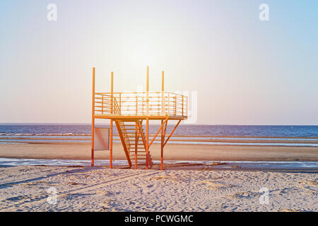 View of sunset sandy beach with red empty modern lifeguard tower station against blue sky in Parnu beach, Estonia - Stock Photo