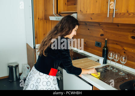 Cute Little Girl Is Cleaning The Kitchen With Yellow Rag - Stock Photo