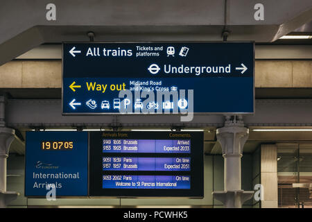 Directional signs and arrival and departure board inside St. Pancras International, London, UK. - Stock Photo